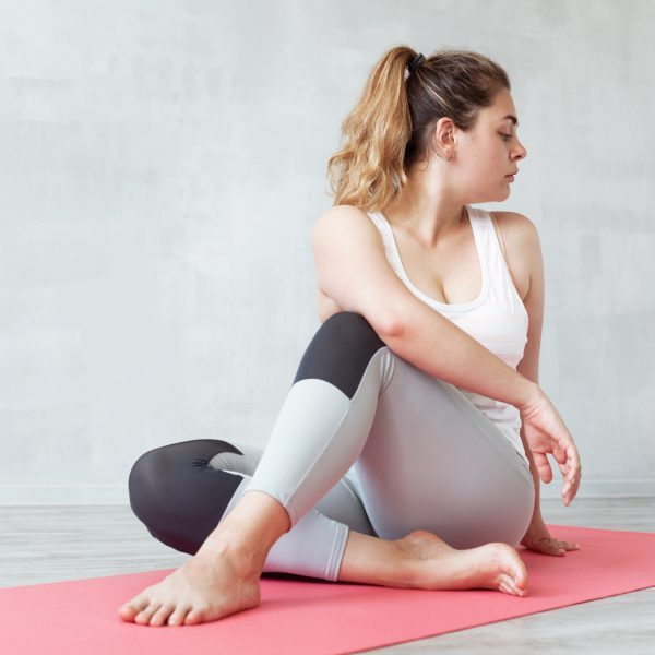 Lovely woman doing stretching or yoga exercise on a mat. Twisted pose